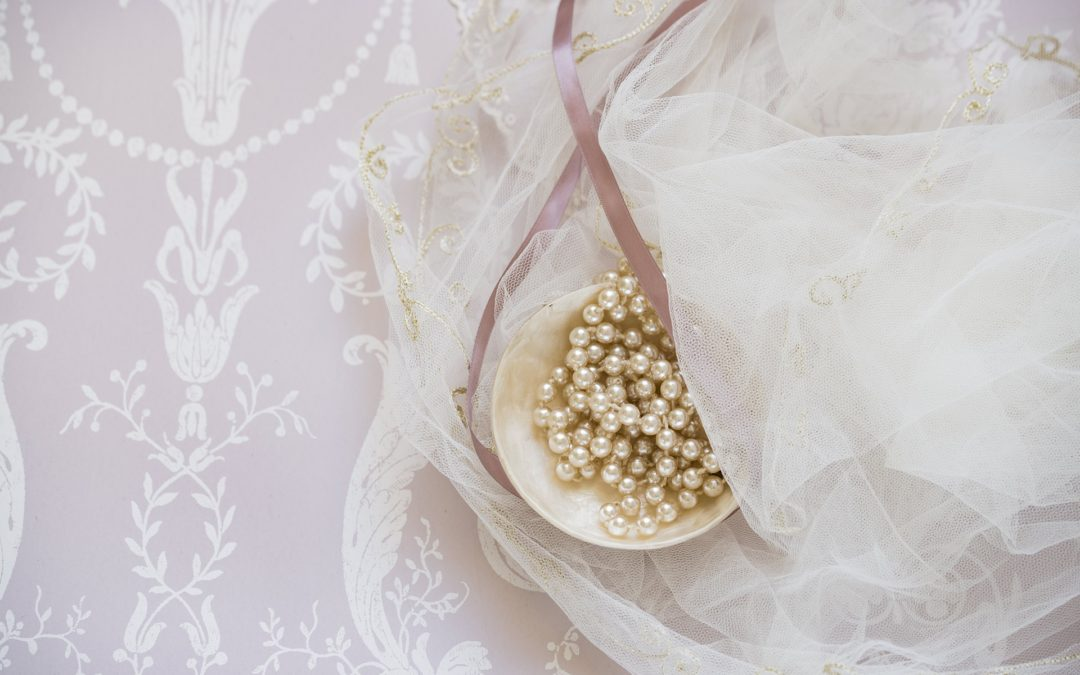 Bowl of pearls with pink ribbon and veil